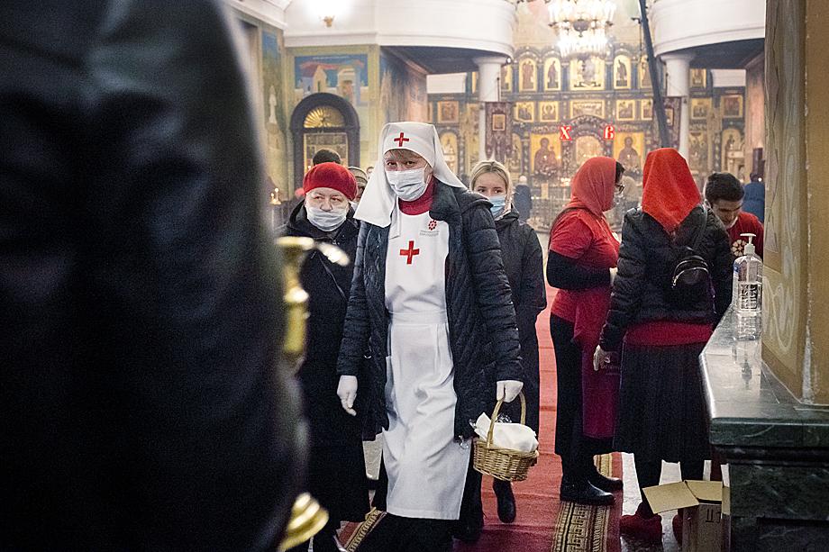 Православная служба милосердия раздаёт прихожанам пасхальное угощение после праздничной литургии.