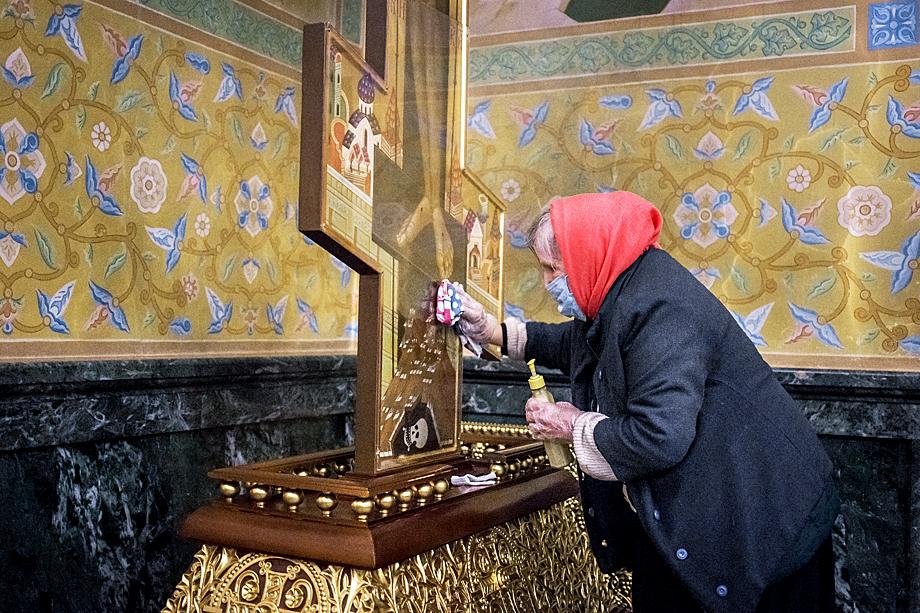 Служительница храма протирает крест антисептическим средством.