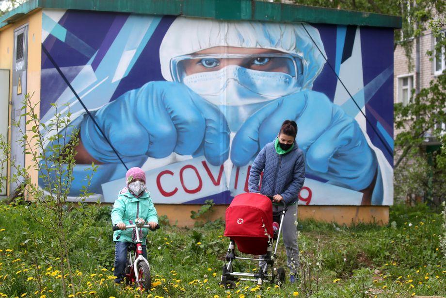 Женщина с детьми на фоне граффити.
