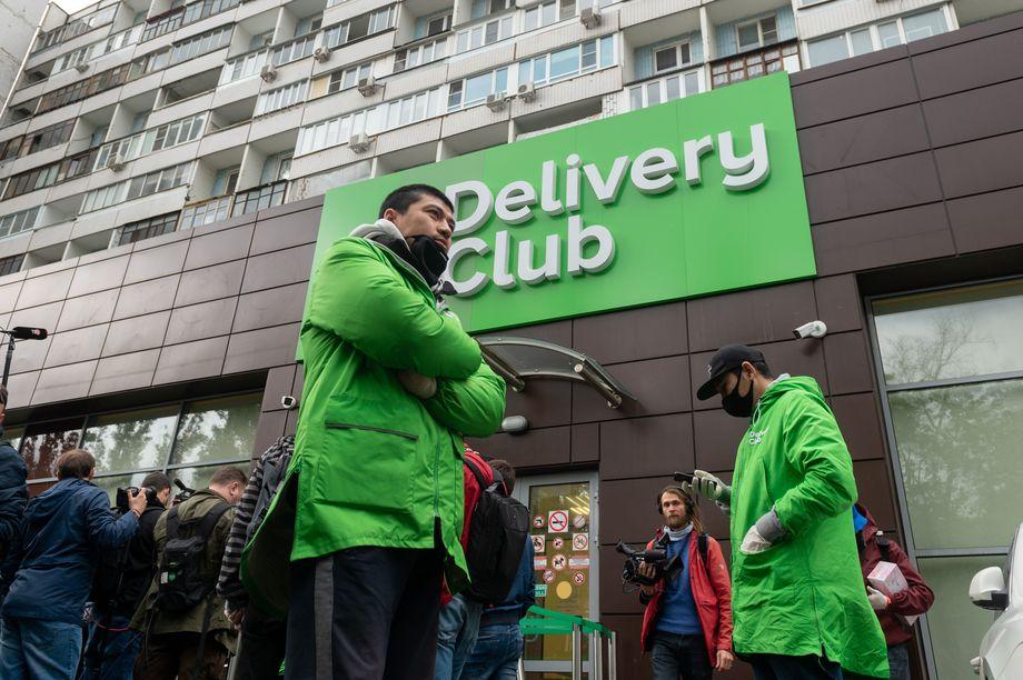Курьеры в рабочей форме пришли к офису Delivery Club.