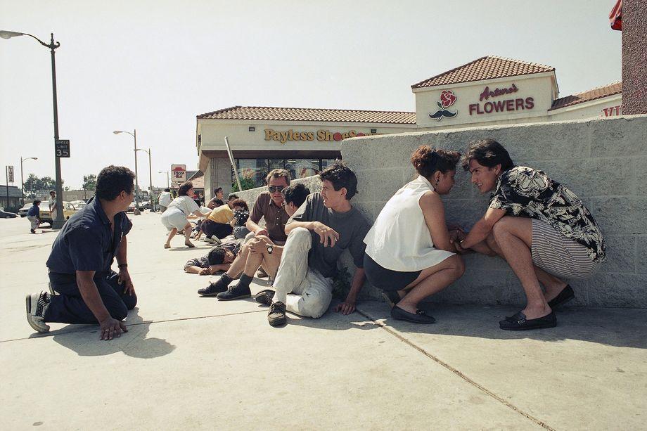 30 апреля 1992 года. Лос-Анджелес. Прохожие прячутся в укрытии от выстрелов во время беспорядков. Владелец корейского магазина стрелял в воздух, чтобы отогнать грабителей.