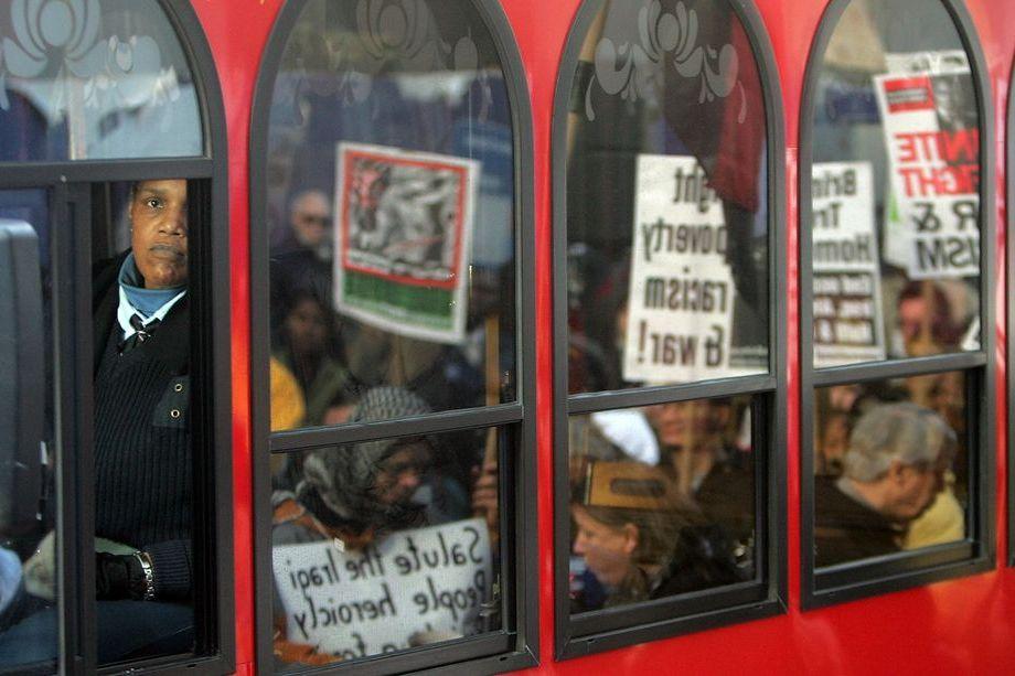 1 декабря 2005 года. Нью Йорк. Марш протеста против бедности, расизма и в честь Розы Паркс отражается в окнах туристического автобуса. 50 лет назад Роза Паркс первой отказалась уступить место в автобусе белому.
