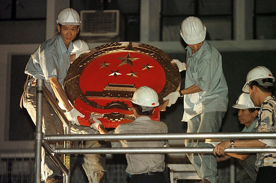 Рабочие размещают эмблему китайского правительства на стене центрального правительственного учреждения в Гонконге после передачи Гонконга Великобританией Китаю.