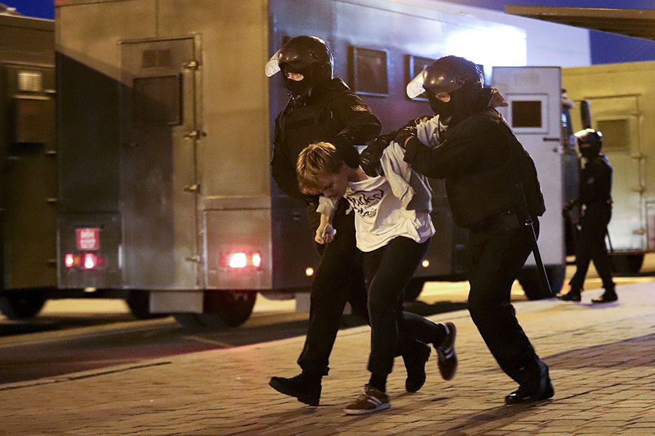 Милиция грубо заталкивает задержанных в автозаки.