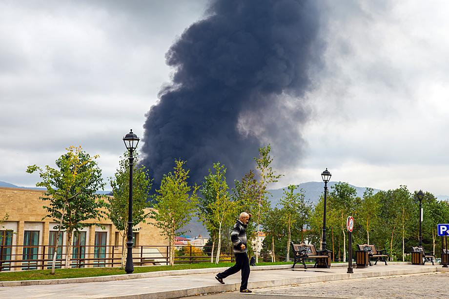 Над городом возвышается чёрный столб дыма, на фоне которого бродят одинокие блаженные старики.