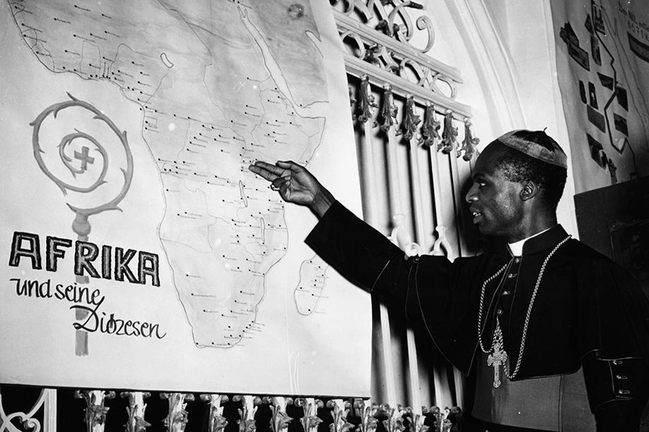 3 июня 1956 года. Лауреан Ругамбва, епископ Рутабо, на выставке миссий в Мюнхене показывает на карте район своей работы в Восточной Африке.
