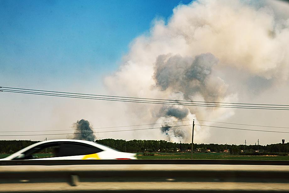 Дым от пожара подобрался к опушке леса, где расположены дома.