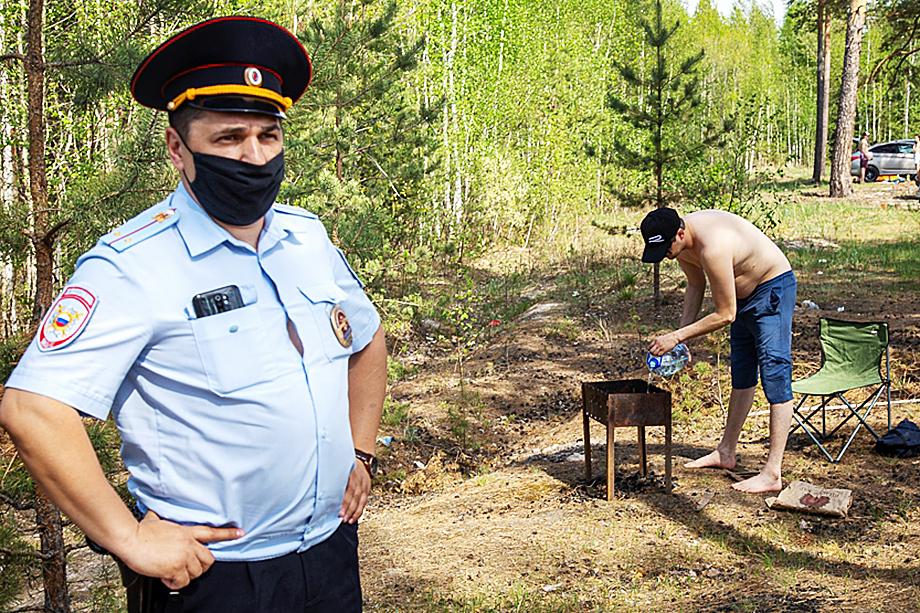Сотрудник полиции требует от нерадивых отдыхающих погасить разведённый огонь.